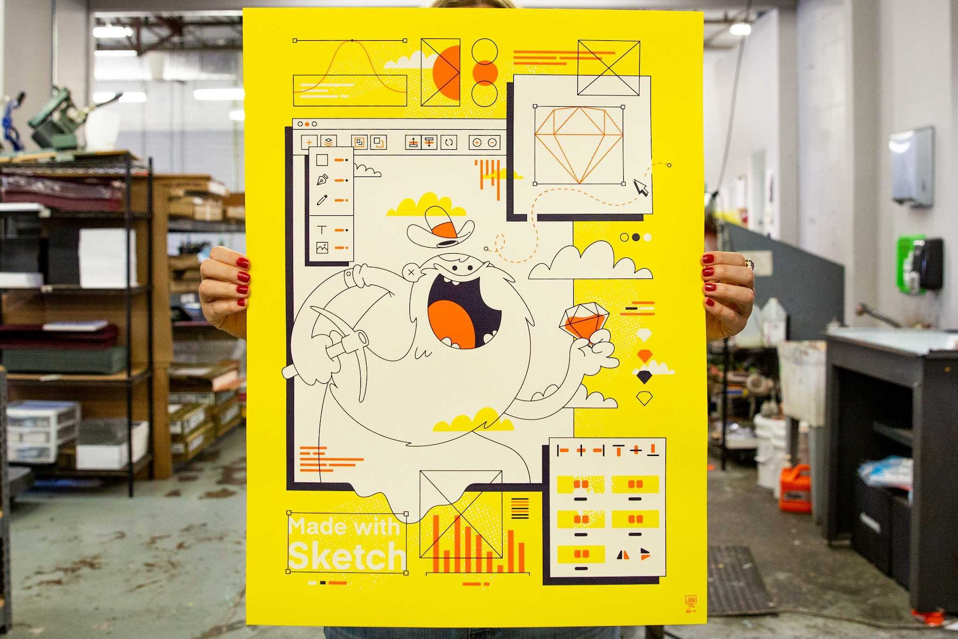 A woman holds up an art print commissioned by Sketch inside a printing studio